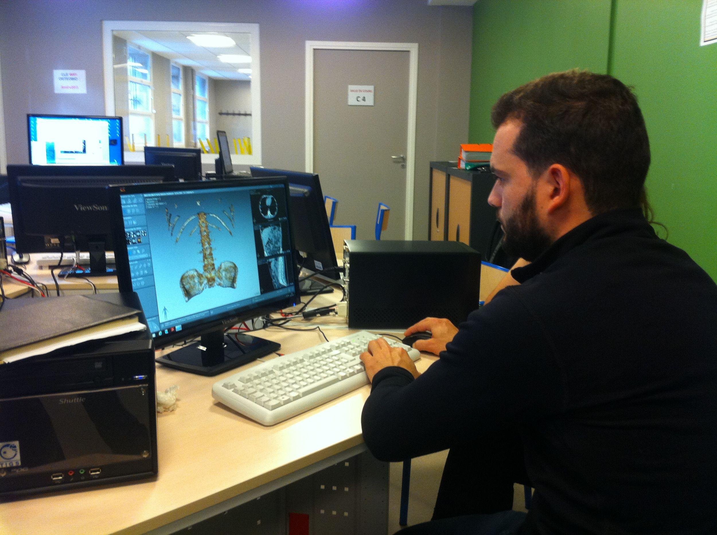 Homme devant un ordinateur dans le laboratoire de recherche de la clinique de cachan de l'école d'ostéopathie Ostéobio Paris
