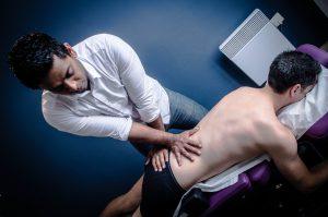 Ramanan Thesingam ostéopathe biomécanicien manipulant un jeune homme allongé sur le ventre de l'école d'ostéopathie Ostéobio Paris