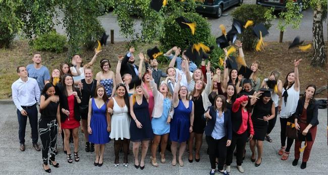 Groupe d'étudiant en fin d'études jetant leur diplôme dans les airs de l'école d'ostéopathie Ostéobio Paris