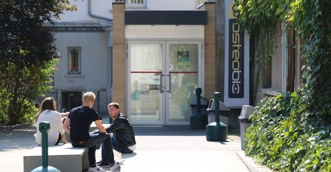 Photo porte d'entrée de l'école d'ostéopathie Ostéobio Paris avec 3 élèves assis devant