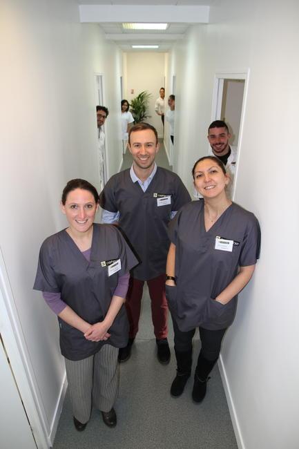 Trois professeurs et leurs élèves derrière eux dans un couloir de l'école d'ostéopathie Ostéobio Paris